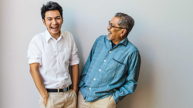 Portrait of Asian senior father and his adult son having fun together and standing on gray backgrounds